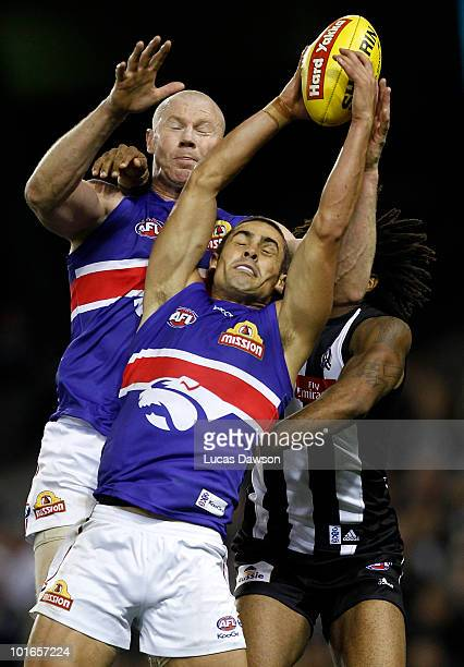 Daniel Giansiracusa and Barry Hall of the Bulldogs attempt a mark during the round 11 AFL match between the Collingwood Magpies and the Western...