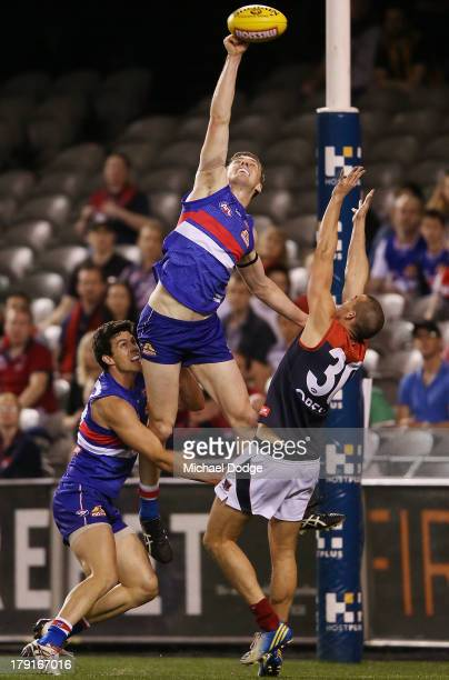 Daniel Giansiracusa and Jordan Roughead of the Bulldogs contest for the ball against James Sellar of the Demons during the round 23 AFL match between...