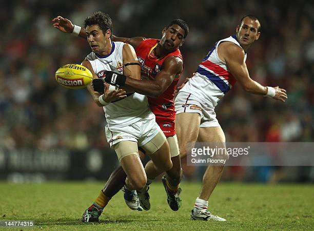 Daniel Giansiracusa of the Bulldogs handballs whilst being tackled by Joel Wilkinson of the Suns during the round eight AFL match between the Western...