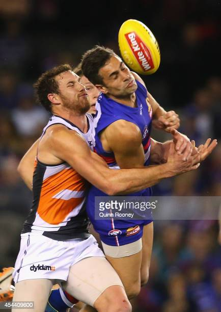 Daniel Giansiracusa of the Bulldogs handballs whilst being tackled by Shane Mumford of the Giants during the round 23 AFL match between the Western...