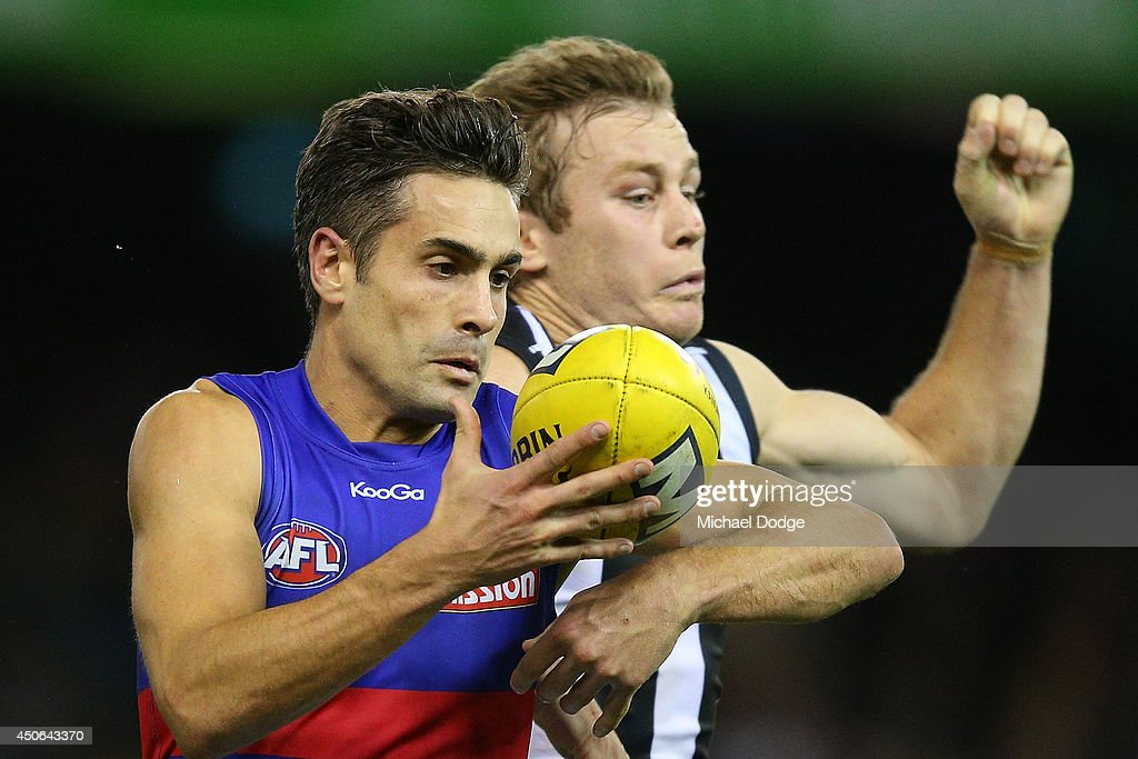 Daniel Giansiracusa of the Bulldogs marks the ball against Sam Dwyer of the Magpies during the round 13 AFL match between the Collingwood Magpies and the Western Bulldogs at Etihad Stadium on June 15, 2014 in Melbourne, Australia.