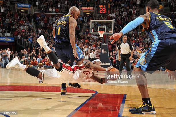 Daniel Gibson of the Cleveland Cavaliers dives for the ball against Chauncey Billups and JR Smith of the Denver Nuggets during the game on February...