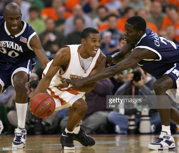 Daniel Gibson of the Texas Longhorns looks to pass between Mo Charlo and Kenny Taylor the Nevada Wolf Pack in the first round of the NCAA Division I...