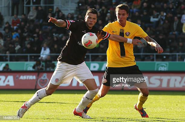 Daniel Ginczek of St. Pauli and Bjarne Thoelke of Dresden compete for the ball during the Second Bundesliga match between FC St. Pauli and Dynamo...