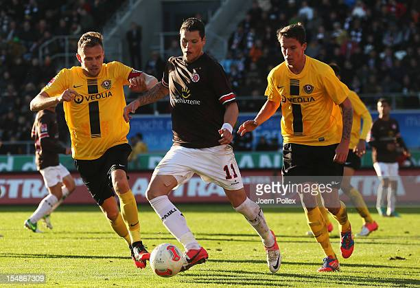 Daniel Ginczek of St. Pauli and Sebastian Schuppan and Bjarne Thoelke of Dresden compete for the ball during the Second Bundesliga match between FC...