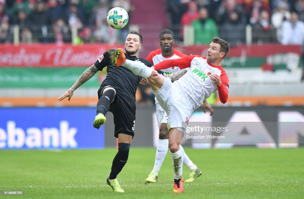 Daniel Ginczek of Stuttgart and Daniel Baier of Augsburg compete for the ball during the Bundesliga match between FC Augsburg and VfB Stuttgart at WWK-Arena on February 18, 2018 in Augsburg, Germany.