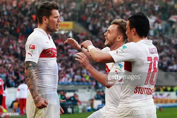 Daniel Ginczek of Stuttgart celebrates his team's second goal with team mates Alexandru Maxim and Filip Kostic during the Bundesliga match between...