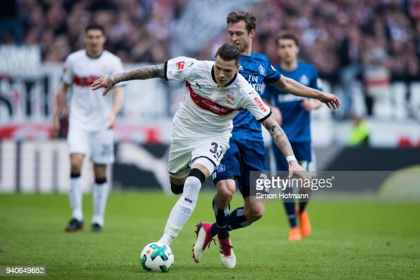 Daniel Ginczek of Stuttgart is challenged by Matti Steinmann of Hamburg during the Bundesliga match between VfB Stuttgart and Hamburger SV at...