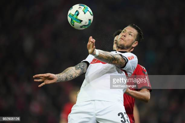 Daniel Ginczek of Stuttgart is challenged by Nicolas Hoefler of Freiburg during the Bundesliga match between SportClub Freiburg and VfB Stuttgart at...