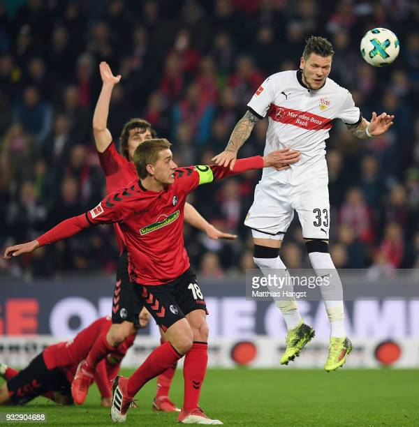 Daniel Ginczek of Stuttgart is challenged by Nils Petersen of Freiburg during the Bundesliga match between SportClub Freiburg and VfB Stuttgart at...