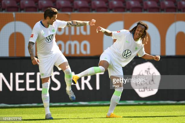 Daniel Ginczek of VfL Wolfsburg celebrates with teammate Kevin Mbabu after scoring his team's second goal during the Bundesliga match between FC...