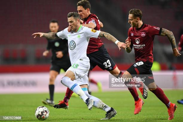 Daniel Ginczek of Wolfsburg is challenged by Lucas Hufnagel and Georg Margreitter of Nuernberg during the Bundesliga match between 1 FC Nuernberg and...