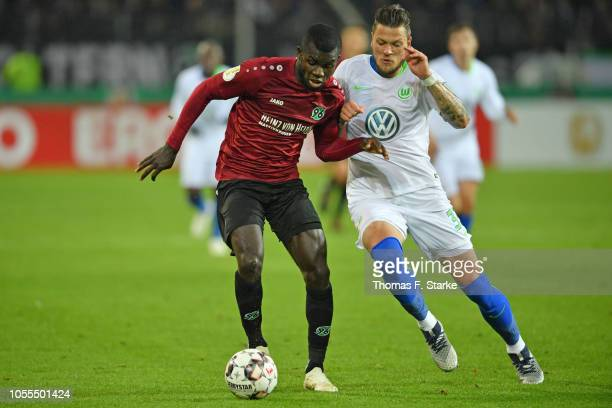 Daniel Ginczek of Wolfsburg tackles Ihlas Bebou of Hannover during the DFB Cup match between Hannover 96 and VfL Wolfsburg at HDIArena on October 30...