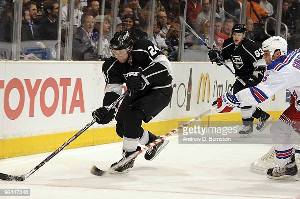 Daniel Girardi of the New York Rangers reaches for the puck as Alexander Frolov of the Los Angeles Kings drives the puck during the game on February...