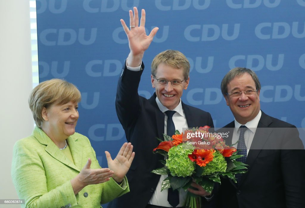 Daniel Guenther, lead candidate of the German Christian Democrats (CDU) in yesterday's state election in Schleswig-Holstein, waves as he arrives for a meeting of the CDU board as German Chancellor and CDU Chairwoman Angela Merkel (L) and CDU lead candidate in upcoming elections in North Rhine-Westphalia Armin Laschet look on at CDU headquarters on May 8, 2017 in Berlin, Germany. The CDU won with nearly a five-point lead over the SPD despite a close race going into the election. Germany will gold federal elections in September.