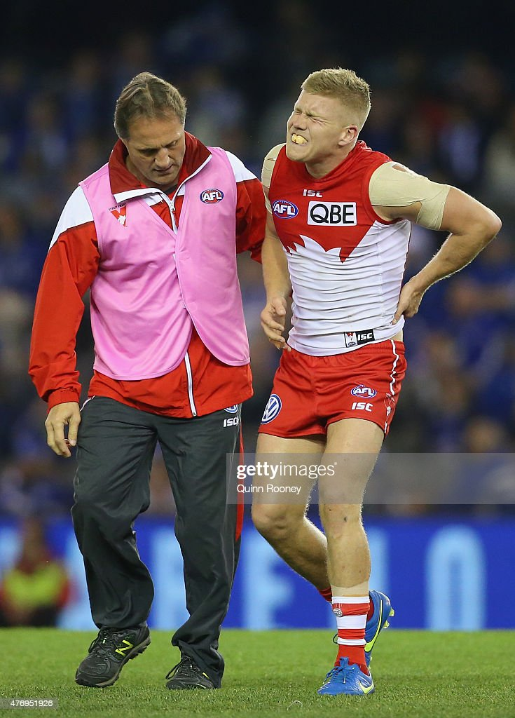Daniel Hannebery of the Swans is helped from the ground by trainers after taking a heavy knock to the back during the round 11 AFL match between the North Melbourne Kangaroos and the Sydney Swans at Etihad Stadium on June 13, 2015 in Melbourne, Australia.