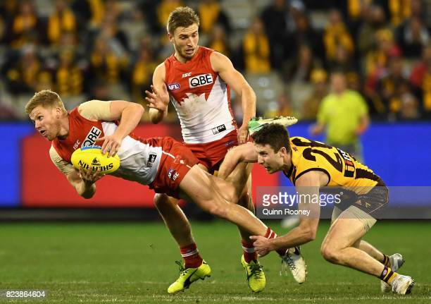 Daniel Hannebery of the Swans is tackled by Liam Shiels of the Hawks during the round 19 AFL match between the Hawthorn Hawks and the Sydney Swans at...