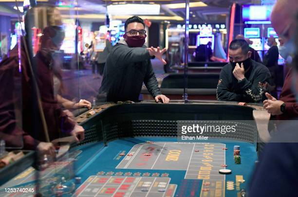 Daniel Hawkins of California rolls the dice at a craps table at Mandalay Bay Resort and Casino after the Las Vegas Strip property opened for the...