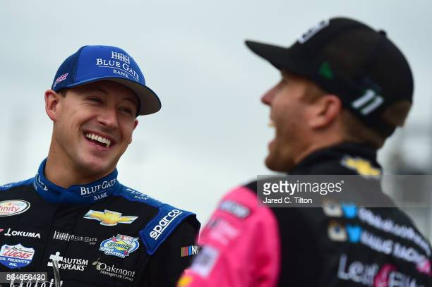 Daniel Hemric driver of the Blue Gate Bank Chevrolet talks to Blake Koch driver of the Breat Cancer Honor Remember Chevrolet on the grid during...