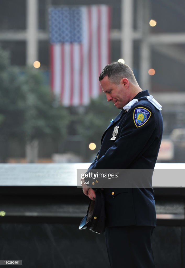 Daniel Henry, a Port Authority of New York/New Jersey police officer, pauses during a moment of silence at 9:01 am EDT, at the South reflecting pool of the 9/11 Memorial during ceremonies for the twelfth anniversary of the terrorist attacks on lower Manhattan at the World Trade Center site on September 11, 2013 in New York City. The nation is commemorating the anniversary of the 2001 attacks which resulted in the deaths of nearly 3,000 people after two hijacked planes crashed into the World Trade Center, one into the Pentagon in Arlington, Virginia and one crash landed in Shanksville, Pennsylvania. Following the attacks in New York, the former location of the Twin Towers has been turned into the National September 11 Memorial & Museum.