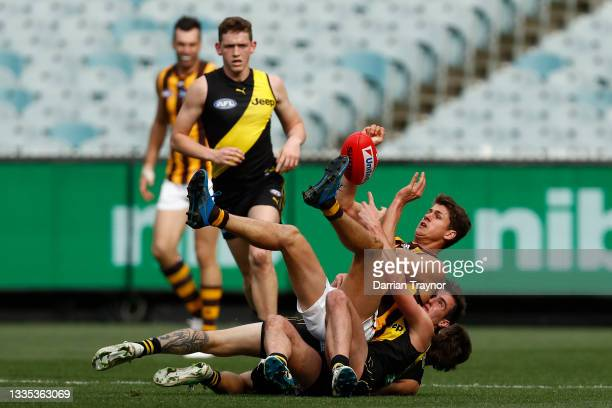 Daniel Howe of the Hawks is tackled by Will Martyn of the Tigers during the round 23 AFL match between Richmond Tigers and Hawthorn Hawks at...