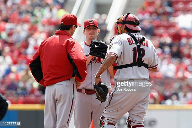 Daniel Hudson of the Arizona Diamondbacks meets at the mound with pitching coach Charles Nagy and catcher Henry Blanco after walking home a run in...
