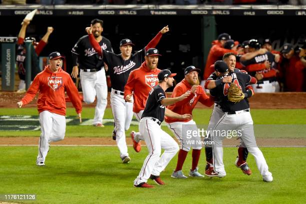 Daniel Hudson of the Washington Nationals and Yan Gomes celebrate with teammates after defeating the St Louis Cardinals to win Game Four of the...