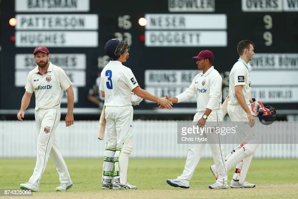 Daniel Hughes of New South Wales and Usman Khawaja shake hand at the end of play on day three of the Sheffield Shield match between Queensland and...