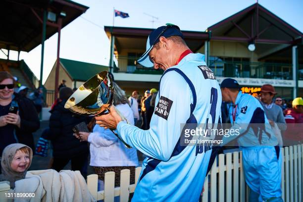 Daniel Hughes of NSW celebrates victory with the trophy during the 2021 Marsh One Day Cup Final match between New South Wales and Western Australia...