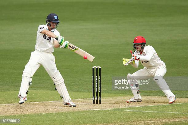 Daniel Hughes of the Blues bats in front of Alex Carey of the SA Redbacks during day one of the Sheffield Shield match between South Australia and...