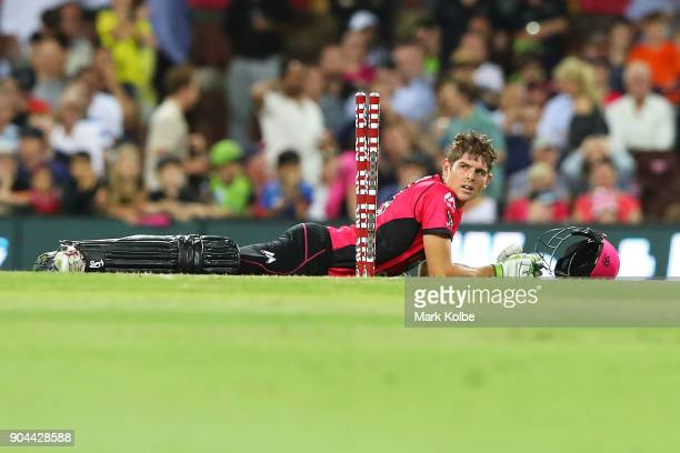 Daniel Hughes of the Sixers looks up at the stumps after diving to make his ground during the Big Bash League match between the Sydney Sixers and the...