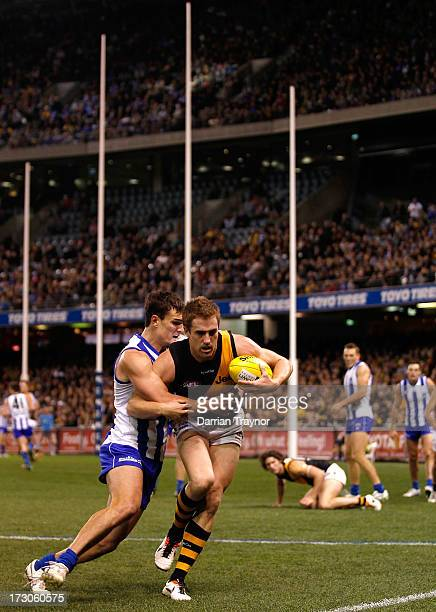 Daniel Jackson of the Tigers is tackled Scott Thompson of the Kangaroos during the round 15 AFL match between the North Melbourne Kangaroos and the...