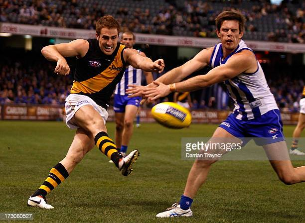 Daniel Jackson of the Tigers kicks the ball as Sam Gibson of the Kangaroos attempts to smother during the round 15 AFL match between the North...