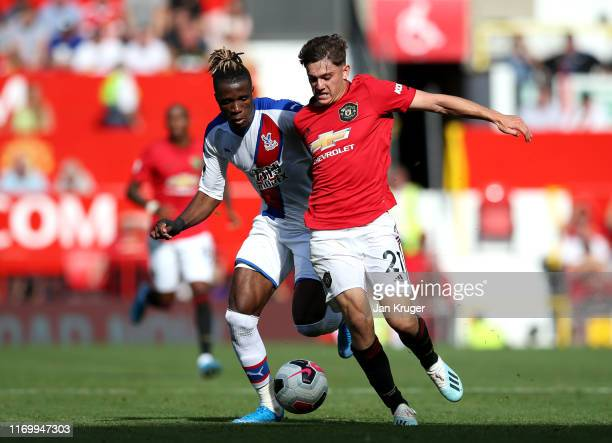 Daniel James of Manchester United is tackled by Wilfried Zaha of Crystal Palace during the Premier League match between Manchester United and Crystal...