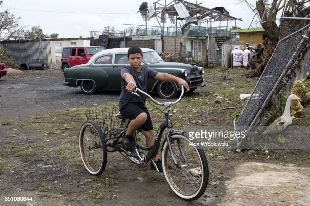 Daniel Joe bikes outside his home the day after Hurricane Maria made landfall September 21 2017 in the Vietnam suburb of San Juan Puerto Rico The...
