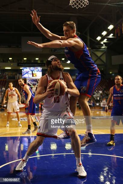 Daniel Johnson of Adelaide tries to block a shot by Larry Davidson of Wollongong during the round 17 NBL match between the Adelaide 36ers and the...