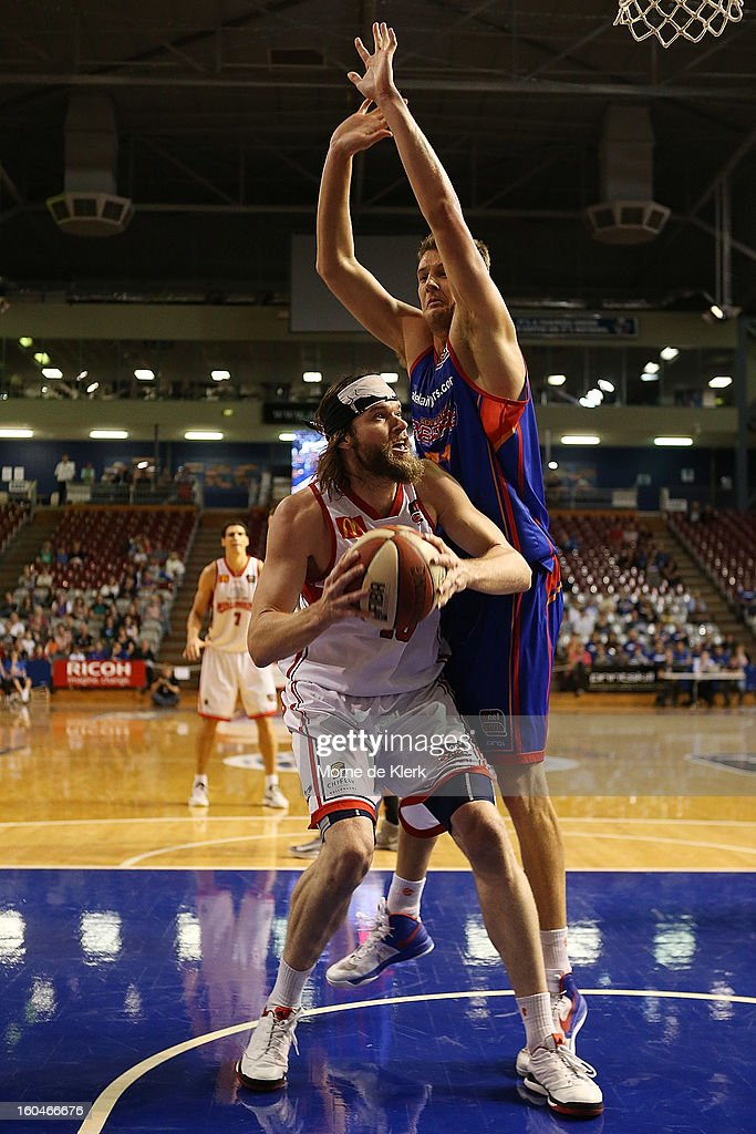 Daniel Johnson of Adelaide tries to block a shot by Larry Davidson of Wollongong during the round 17 NBL match between the Adelaide 36ers and the Wollongong Hawks at Adelaide Arena on February 1, 2013 in Adelaide, Australia.