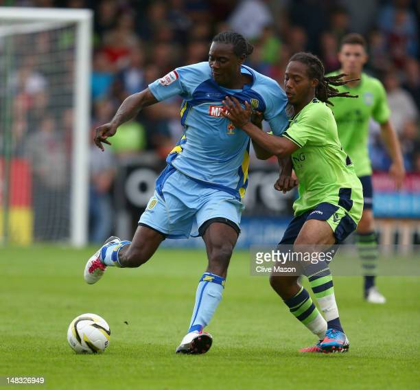Daniel Johnson of Aston Villa holds off a challenge from Calvin Zola of Burton Albion during the pre season friendly match between Burton Albion and...