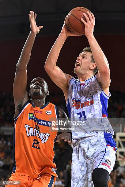 Daniel Johnson of the 36ers drives towards the basket under pressure from Nnanna Egwu of the Taipans during the round 10 NBL match between the Cairns...