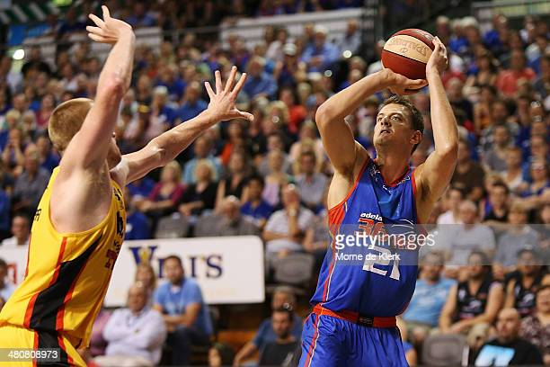 Daniel Johnson of the 36ers shoots for three points under pressure from Adam Ballinger of the Tigers during game one of the NBL Semi Final series...