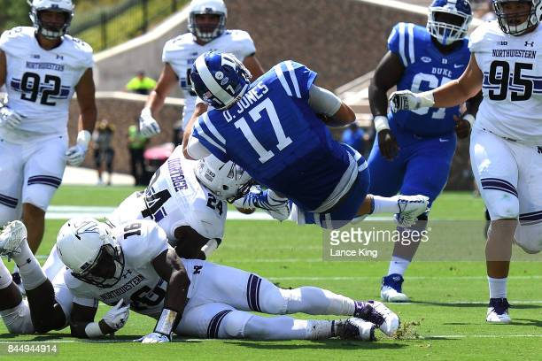 Daniel Jones of the Duke Blue Devils is tackled by Montre Hartage and Godwin Igwebuike of the Northwestern Wildcats at Wallace Wade Stadium on...