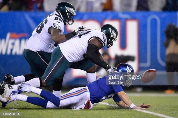 Daniel Jones of the New York Giants fumbles the ball as Fletcher Cox of the Philadelphia Eagles chases and recovers the ball on the New York Giants...