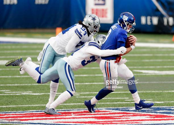 Daniel Jones of the New York Giants in action against Randy Gregory and Donovan Wilson of the Dallas Cowboys at MetLife Stadium on January 03, 2021...