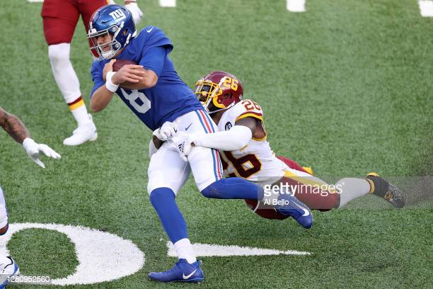 Daniel Jones of the New York Giants is tackled by Landon Collins of the Washington Football Team during their NFL game at MetLife Stadium on October...