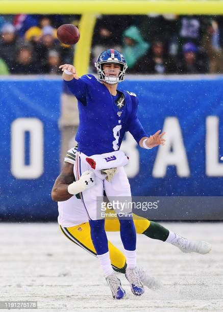 Daniel Jones of the New York Giants makes a pass while tackled by Za'Darius Smith of the Green Bay Packers during the first half of their game at...
