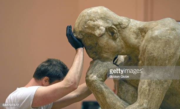 Daniel Joseph holds onto a rare plaster cast of Rodins 'The Thinker' while moving the sculpture to rest on a pedestal in Salem MA on Apr 25 2016 On...