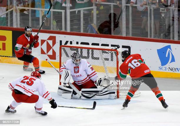 Daniel Koger of Hungary shoots next to goalie Przemyslaw Odrobny of Poland and Mikolaj Lopuski of Poland during the 2018 IIHF Ice Hockey World...