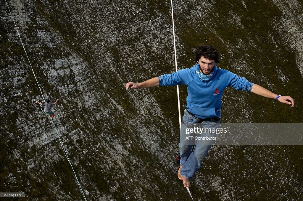 Daniel Laruelle of South Africa (R) and Sebastian Gum Chung Segraves (L) walk on lines during the Highline Extreme event in Moleson peak, western Switzerland on September 15, 2017. Fifty of the Worlds best slackliners compete until September 17, 2017 on six different lines ranging from 45 metres to 304 metres. / AFP PHOTO / Michael Buholzer