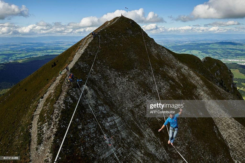 Daniel Laruelle of South Africa walks on the line during the Highline Extreme event in Moleson peak, western Switzerland on September 15, 2017. Fifty of the Worlds best slackliners compete until September 17, 2017 on six different lines ranging from 45 metres to 304 metres. / AFP PHOTO / Michael Buholzer