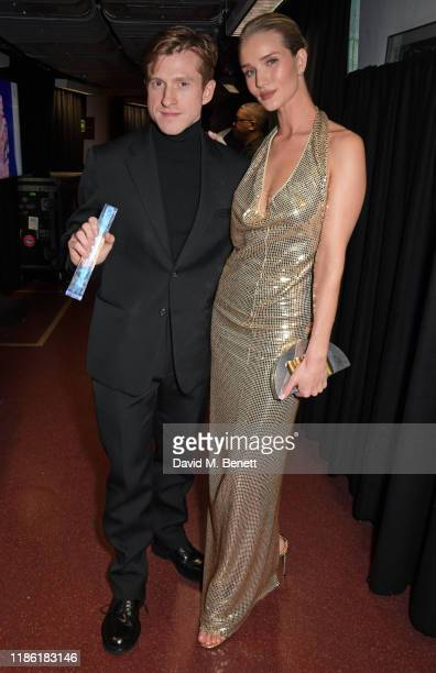Daniel Lee, accepting the Accessories Designer of the Year award on behalf of Bottega Veneta, and Rosie Huntington-Whiteley pose backstage stage...